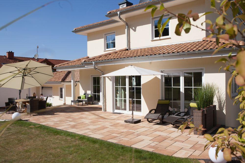 Blick auf die mediterran gestaltete Terrasse mit Liegestühlen und Sitzecke vor großen Fenstern des Wohnzimmers.