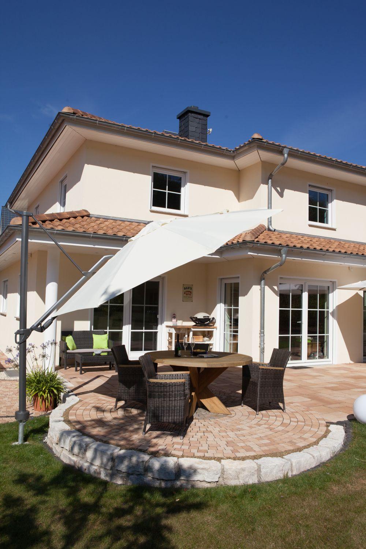 Ein runder gestalteter Sitzbereich mit Sonnenschirm ist in die Terrasse mit Medino Platten integriert.