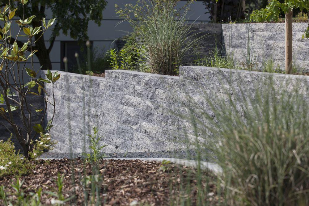 Blick auf die Catania Mauer in 12 Steinlagen mit Gräser-Hinterbepflanzung, Kiesrampen und Rindenmulch als Beetabdeckung.