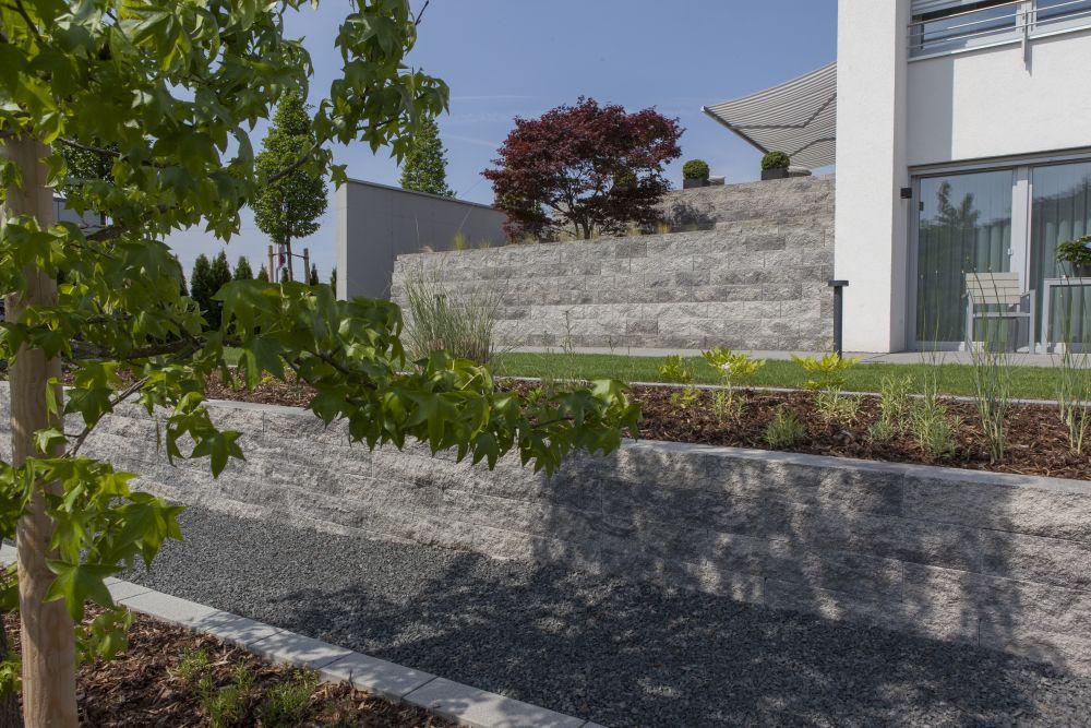 Solitärbäume in den Beeten, kleine Sträucher, Lavendel und Gräser eingepflanzt in den Beeten im Eingangsbereich.