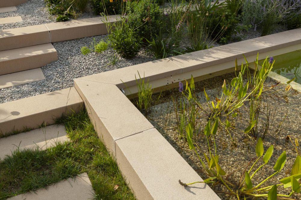 Detailaufnahme des angelegten Teiches und angrenzendem Treppenanlage im Garten.