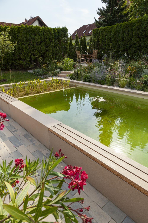 Der Teich im Vodergrund mit abwechslungsreicher Beetbepflanzung und kleiner Sitzecke im Hintergrund.