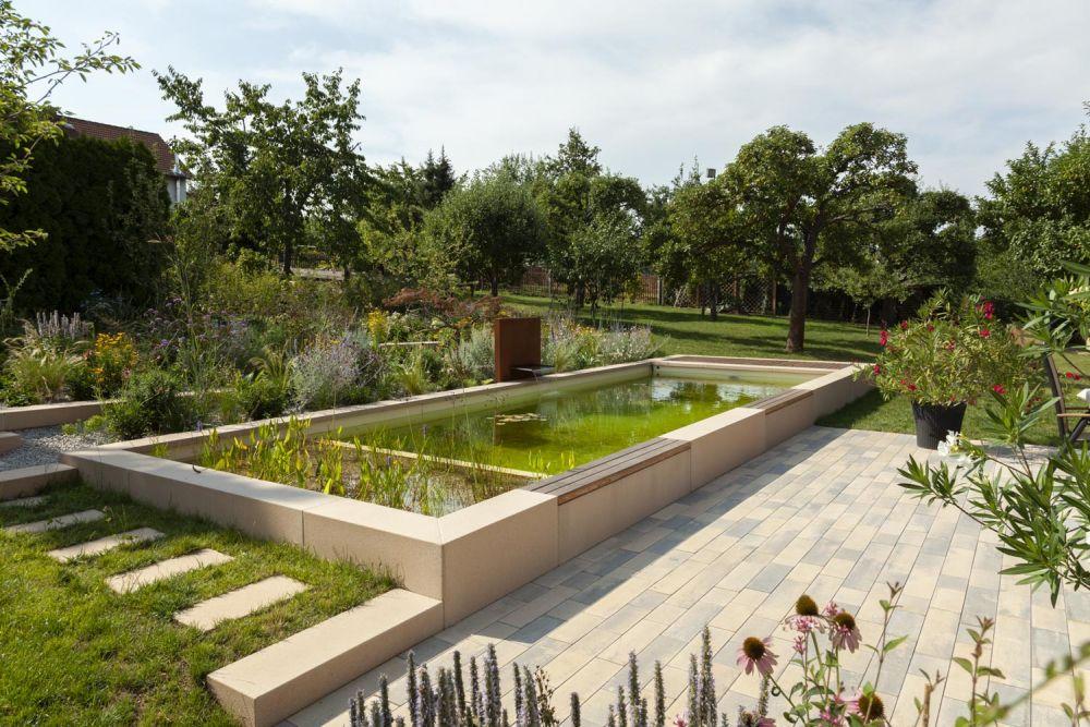 Blick auf den Teich mit Cortenstahl-Brunnen und die gepflasterte Terrasse.