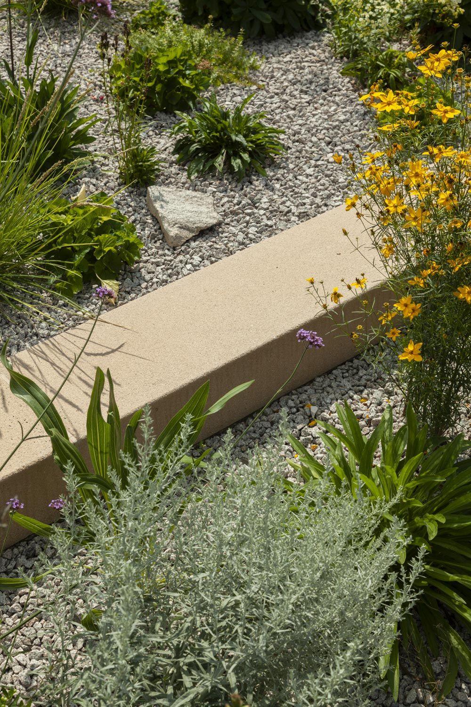 Nahaufnahme einer Blockstufe in Maßanfertigung im kiesbeet mit üppiger Bepflanzung.