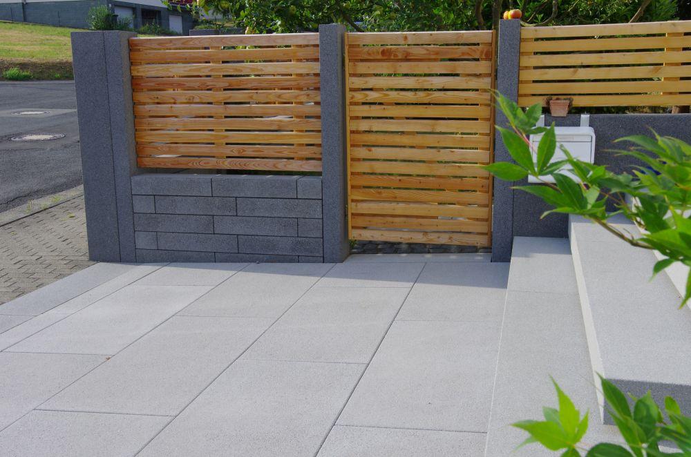Blick auf die halbhohe Betonsteinmauer mit Holzbalken on top als Zaun und Sichtschutz des Grundstücks.