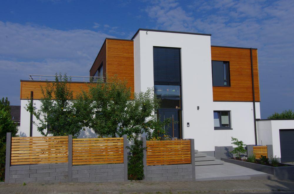 Gesamtaufnahme des Neubaus und der gestalteten Außenanlagen von der gegenüberliegenden Straßenseite aus.