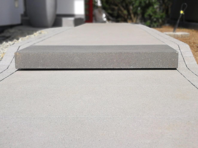Detailbild einer Beton-Außentreppe mit rauer Oberflächenstruktur.