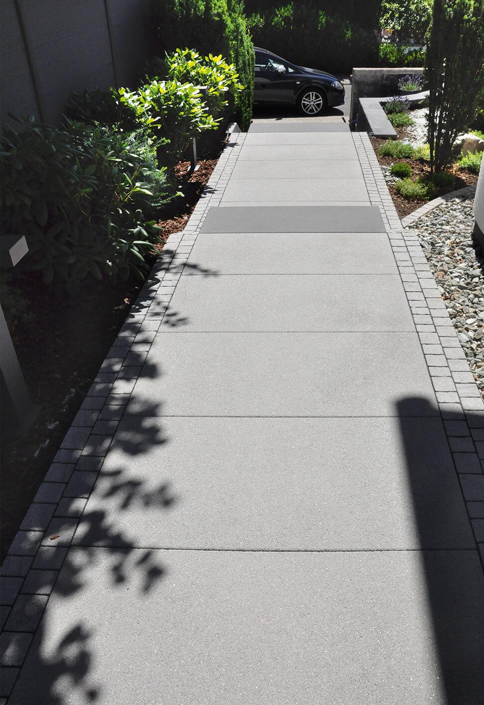 Blick auf den langen Weg mit großformatigen Platten, der entlang des Hauses bis zum geparkten Auto führt.
