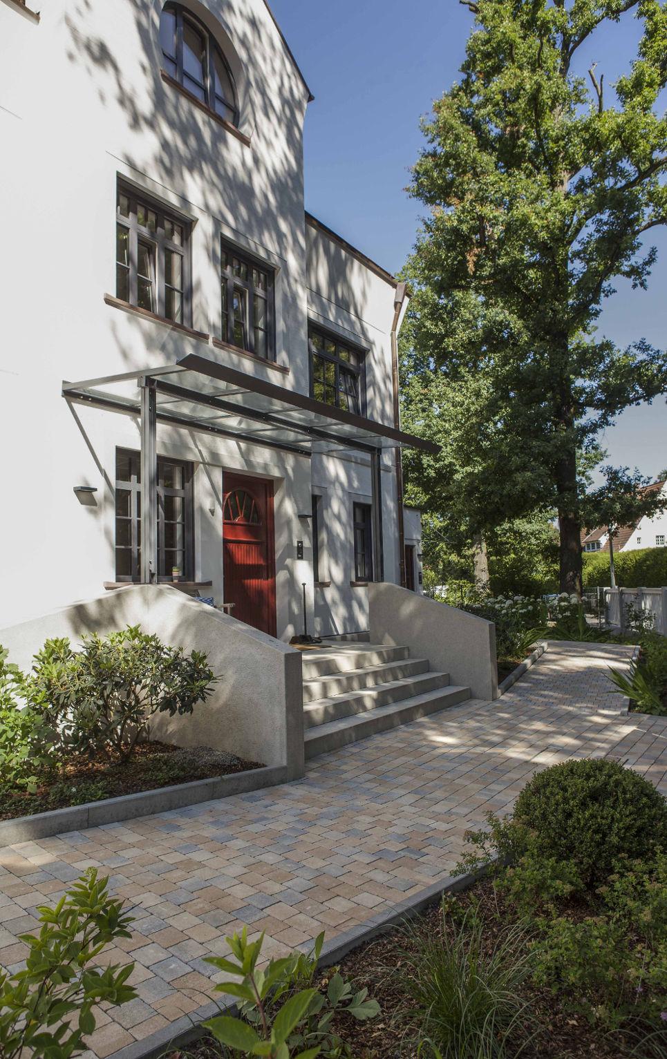 Klassischer Neubau mit roter Haustür, Glasvordach und einer breiten Außentreppe.