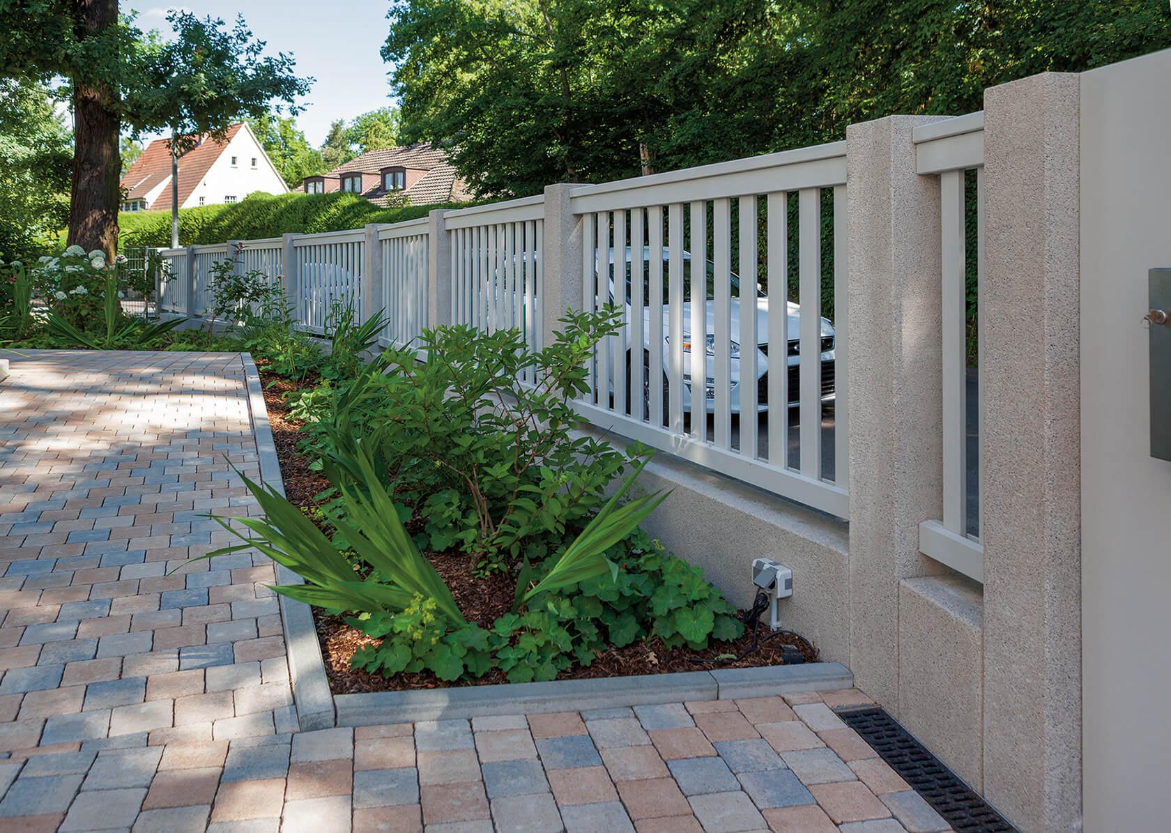 Maßangefertigte Betonpfeiler für den Zaun mit Metallstreben, der das Grundstück einfasst.