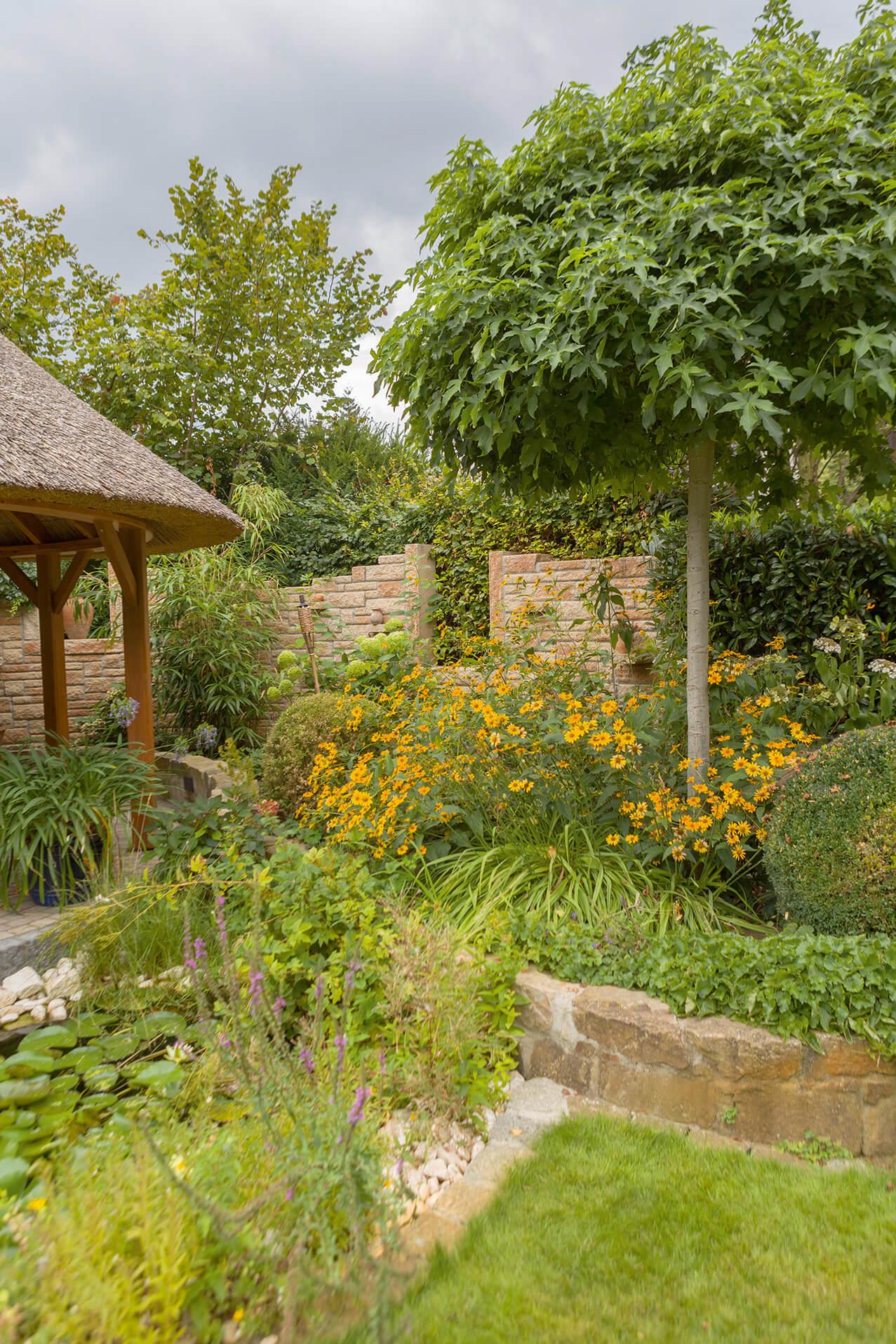 Viele Stauden, Bodendecker und Bäume gestalten den Garten im mediterran-rustikalen Stil mit Pergola und wild aufgesetzter Toskana Mauer.