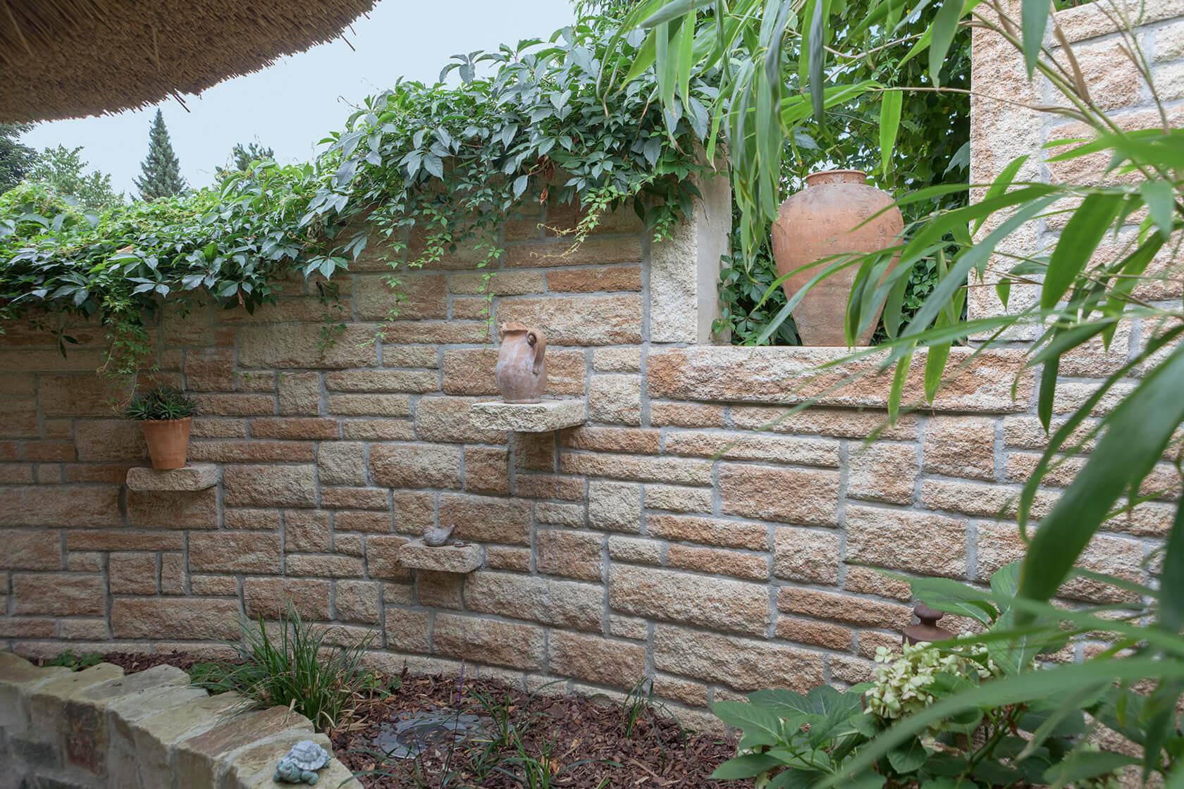 Gartengestaltung im mediterranen Stil mit einer wild aufgesetzten Steinmauer.