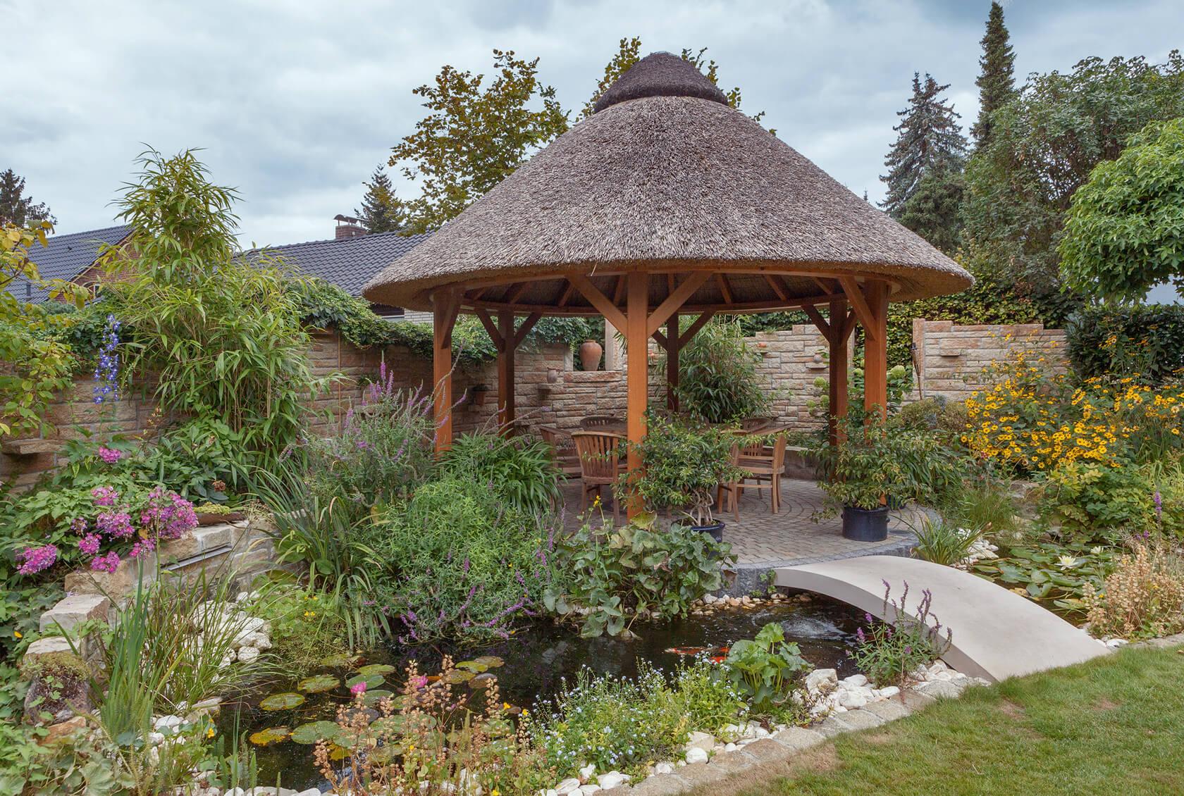 Naturnahe Gartengestaltung mit vielen Pflanzen und einem kleinen Teich. Die runde Pergola mit Strohdach fügt sich harmonisch ins Bild ein.