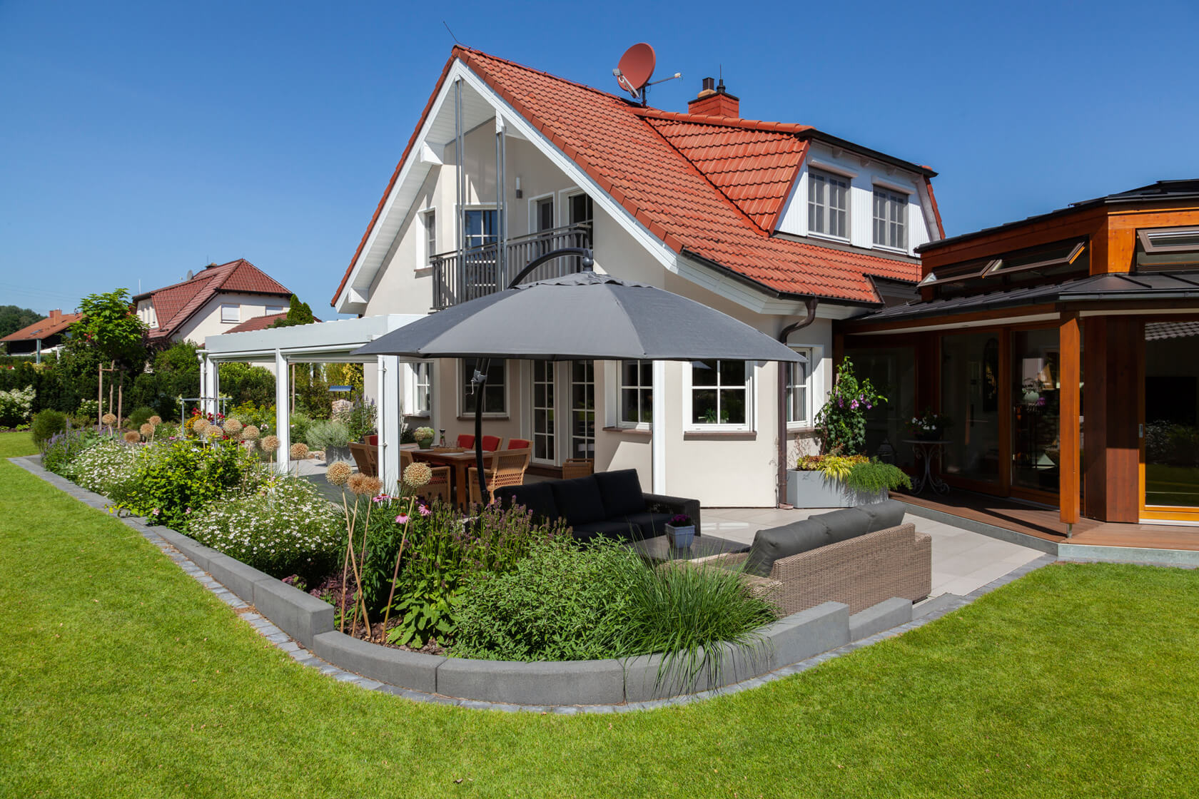 Blick auf die Terrasse und das Haus von der Wiese aus. Ein Blumenbeet grenzt Rasen und Sitzbereich voneinander ab.