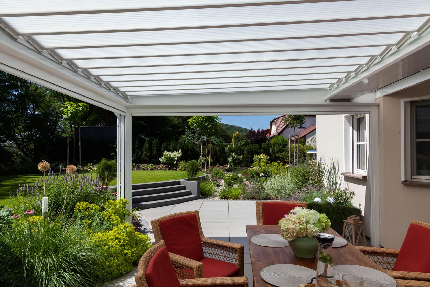 Die Terrasse hat einn überdachten Sitzbereich und erstreckt sich bis zur Außentreppe, die auf die höher gelegene Rasenfläche führt.
