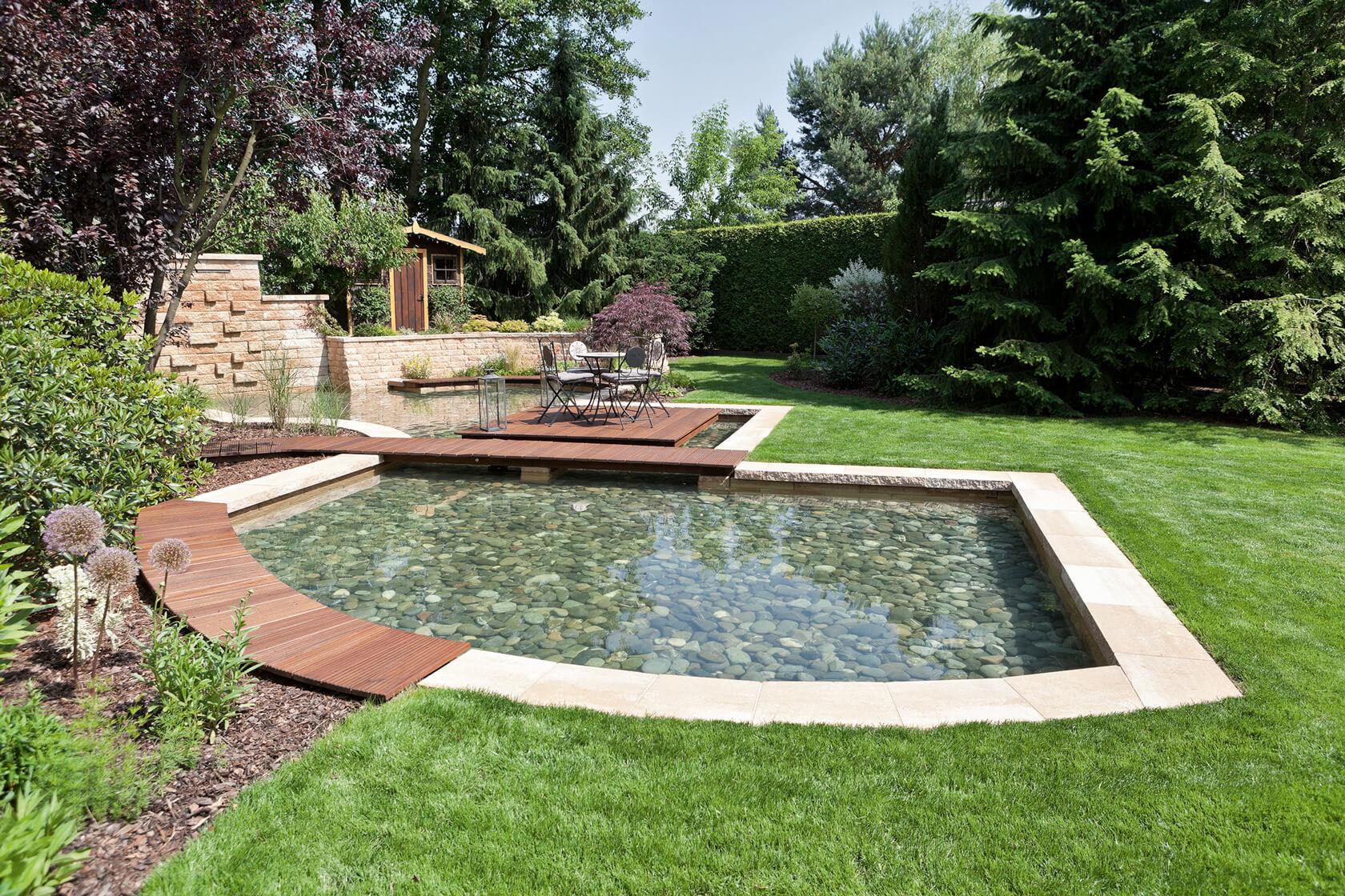 Der in zwei Flächen unterteile Teich wird auf einer Seite mit einer Steinmauer eingefasst. Auf einem Holzdeck kann man auf dem Wasser sitzen.