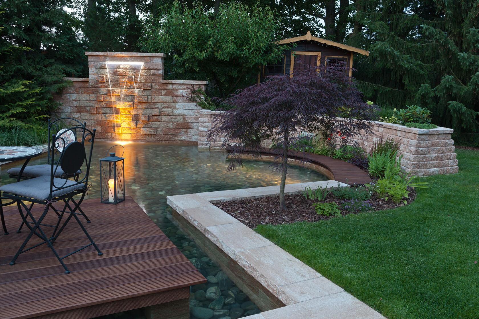Abendaufnahme der Steinmauer mit Wasserfallschütte und Sitzplatz vor dem angelegten Teich.