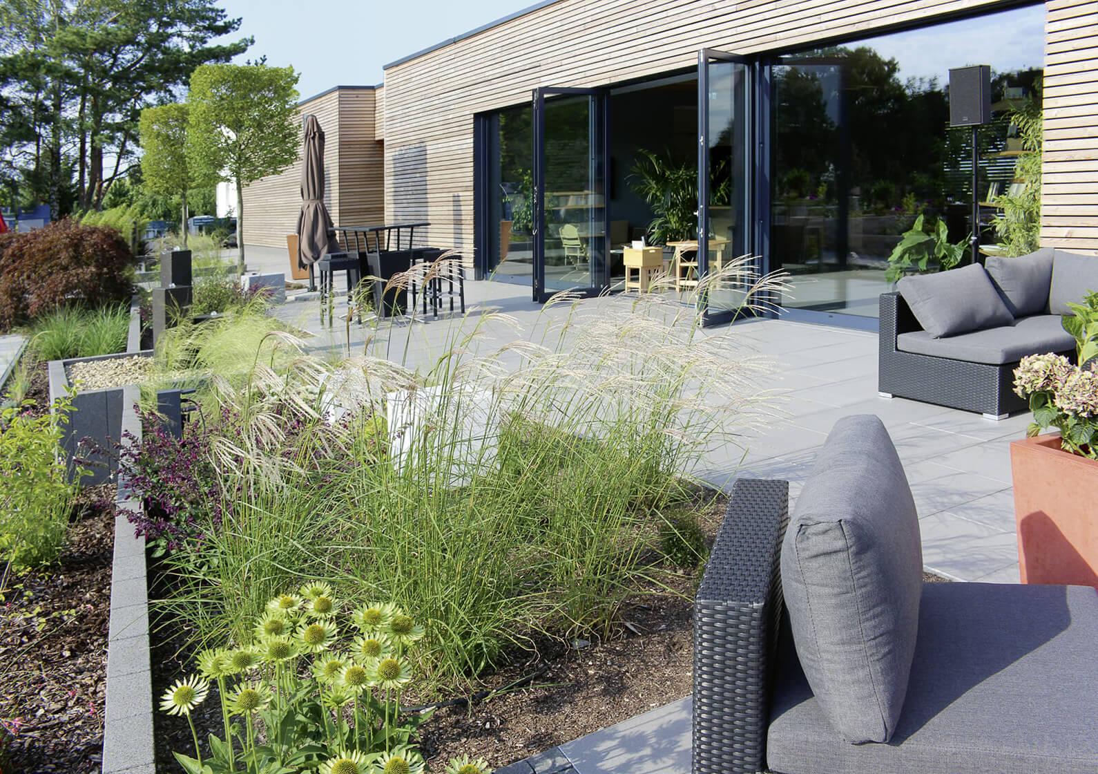 Eingangsbereich des Ideengartens Berlin mit Terrassenplatten, Beeten mit Gräsern und Loungemöbeln.