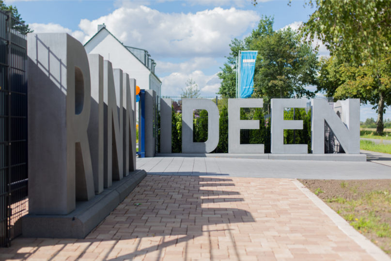 """Die großen Betonbuchstaben mit dem Schriftzug """"Rinn Ideengarten"""" am Eingang zum Gelände des Ideengartens Berlin."""