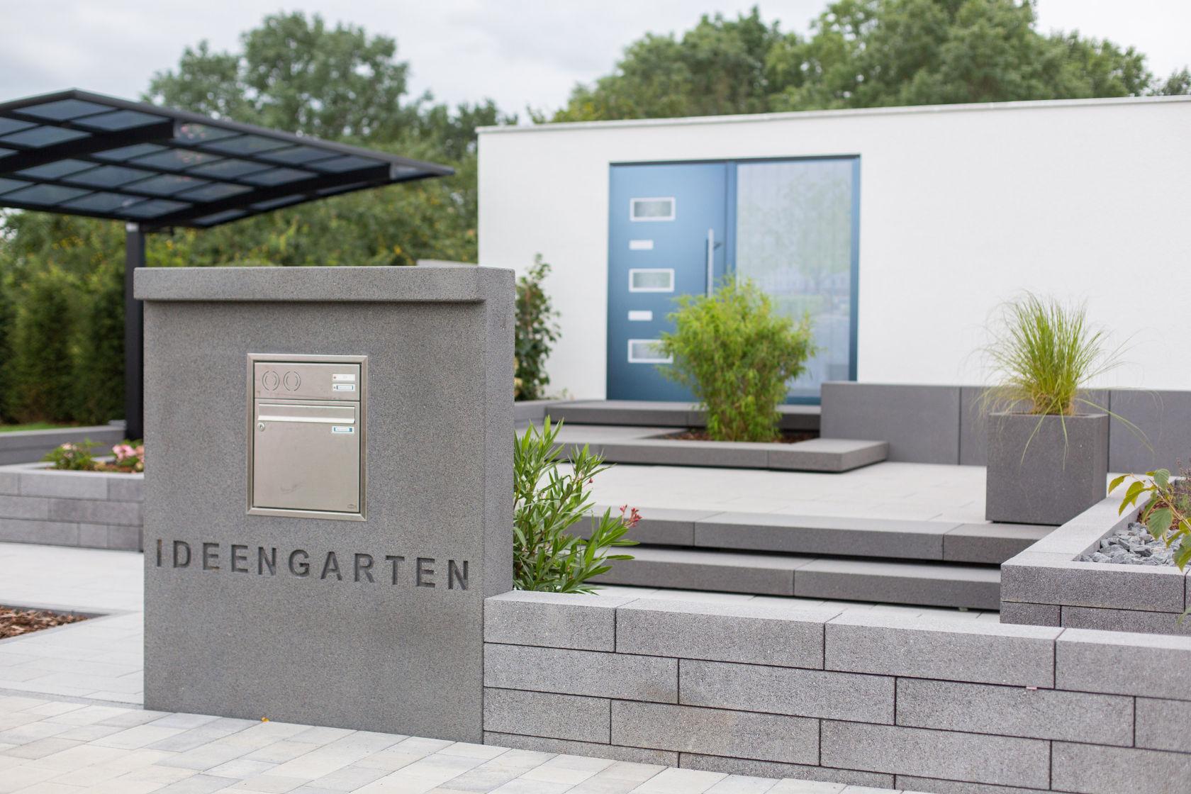 Der Briefkasten ist hier in das Beton-Mauerteil-Element integriert, das Grundstück wird von einer Mauer eingefasst. Die grau gewählten Gestaltungselemente für den Vorgarten passen zum modernen Stil.