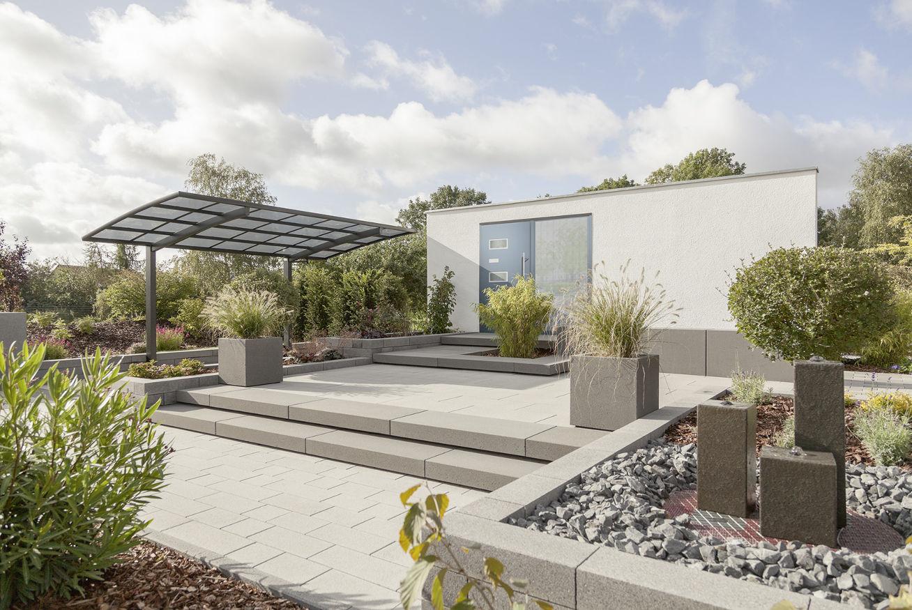 Blick auf den Hauseingangsbereich im Ideengarten Berlin. Der moderne Vorgarten wird ergänzt mit Carportdach, Brunnen und einer weitläufigen Außentreppe.