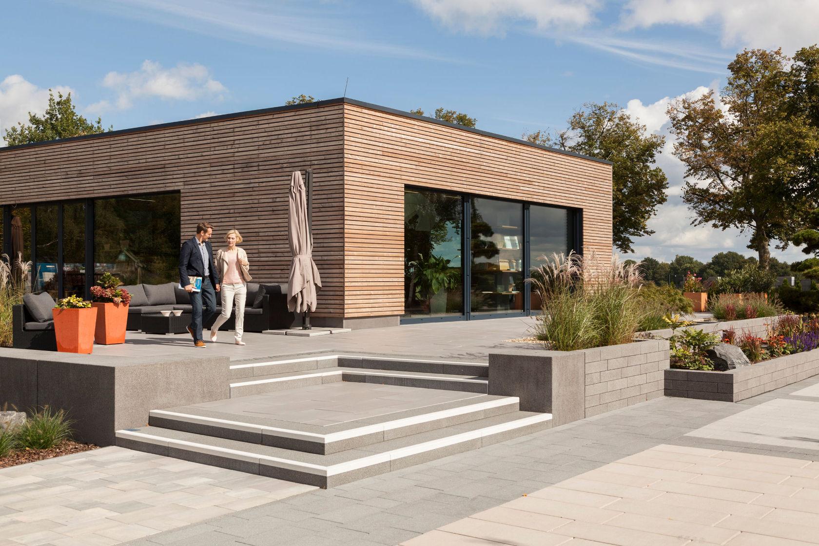 Der Ideenpavillon ist ein modernes Gebäude mit Flachdach und Holzfassade. Die Bauherren begeben sich gerade über die Treppenstufen auf das Ideengarten-Gelände.