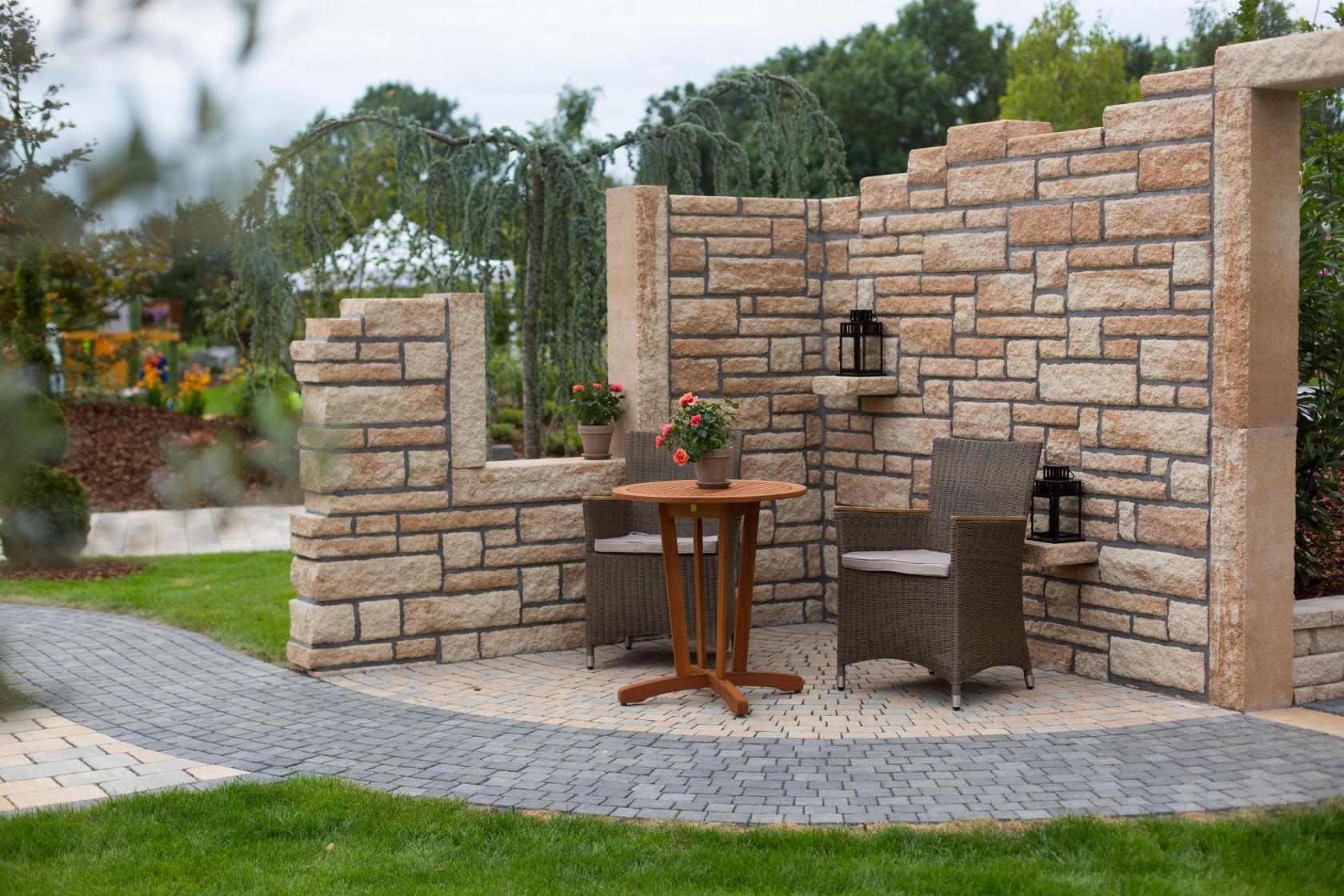 Ruinenmauer und Holzmöbel für eine mediterrane Sitzecke im Garten.