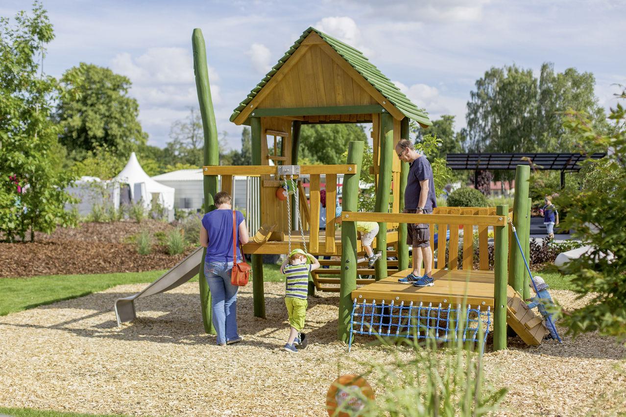 Ein Holz-Spielturm im Ideengarten Berlin für die kleinen Besucher.