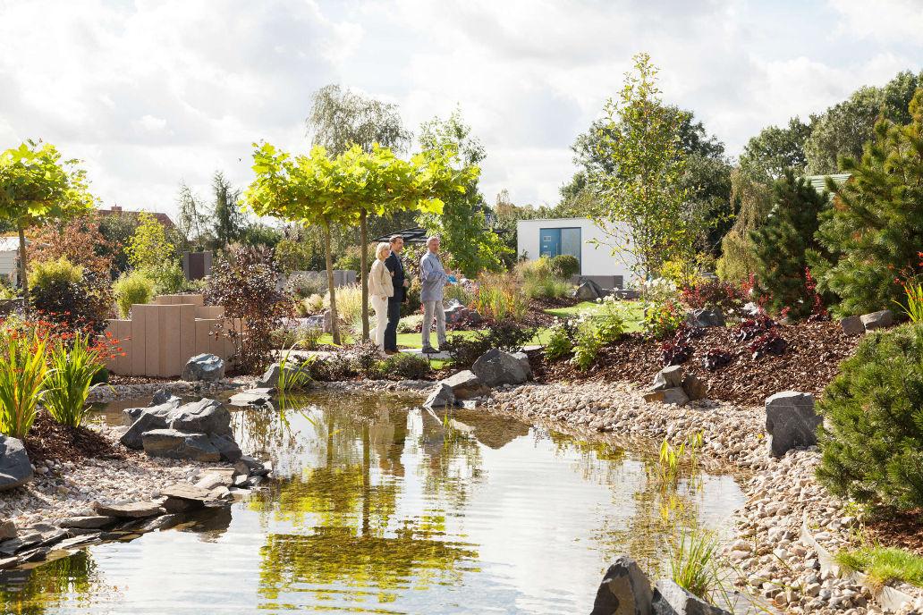 Bauherren erkunden zusammen mit dem Rinn Gartenberater das Gelände und finden Gestaltungsideen für das eigene Zuhause. Ins Kiesbett ist hier ein kleiner Teich integriert.