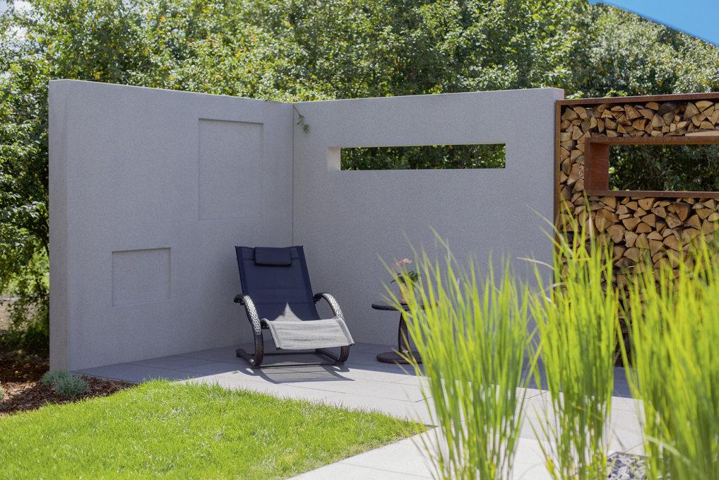 Moderne Sitzecke mit Loungeliege im Grünen und Mauerteil als Sichtschutz für Privatsphäre auf der Terrasse.