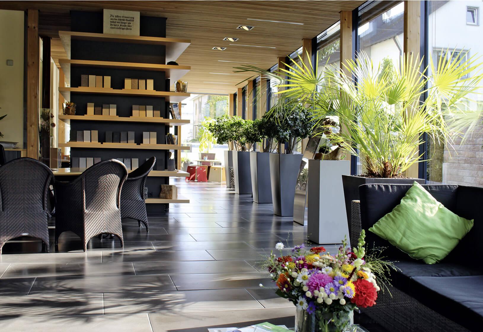 Auf den Sofas kann man im Ideenpavillon Platz nehmen, während sich die Gartenberater an den Schreibtischen in einer Beratung befinden.