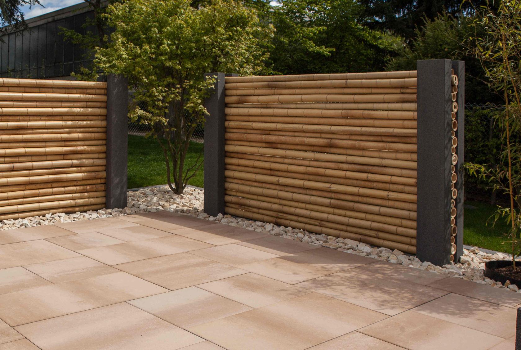 Bambusstäbe werden hier horizontal gestapelt und von Vario-Blocs eingefasst: Ein Sichtschutz der besonderen Art.
