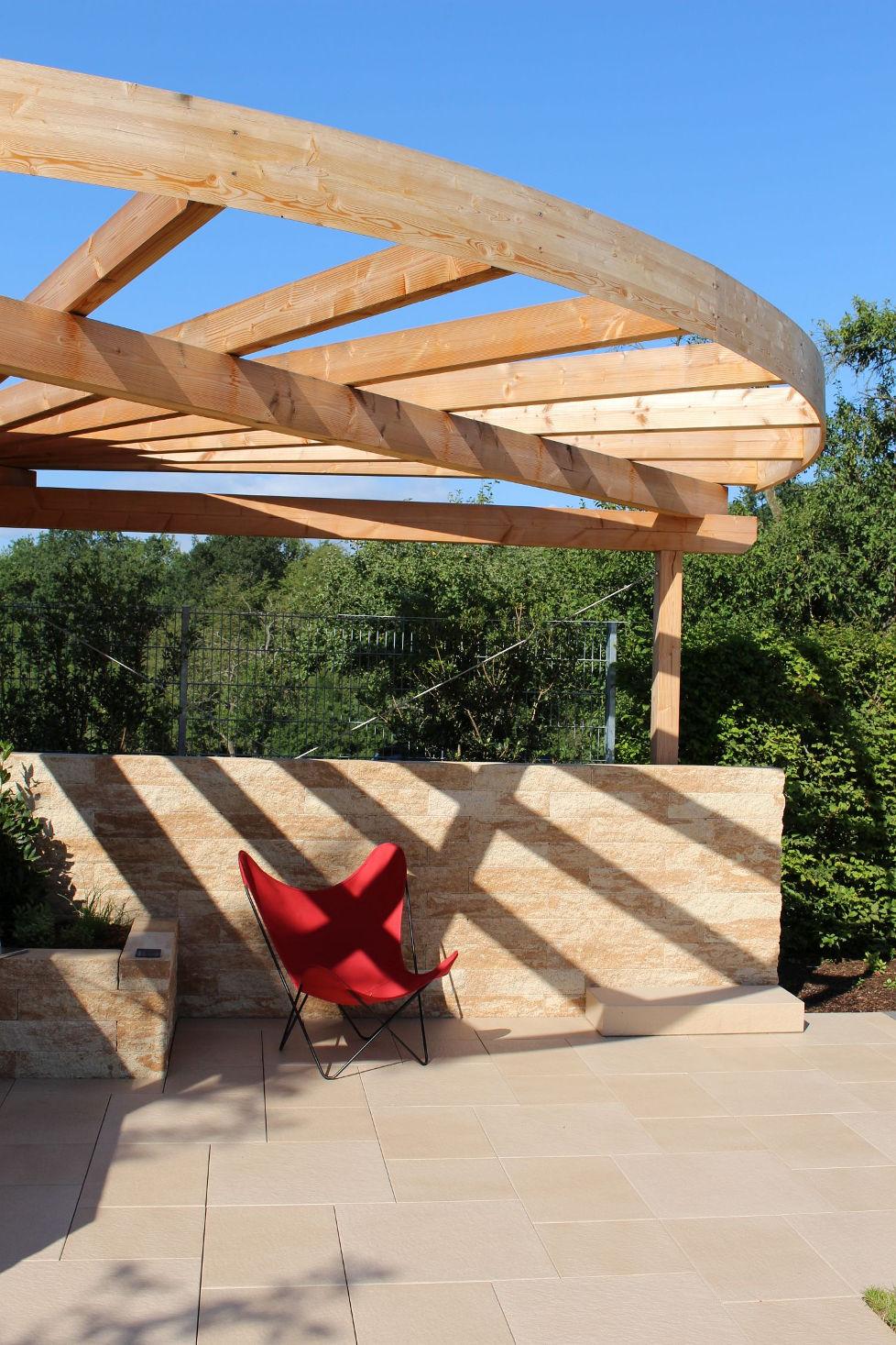Roter Stuhl in mediterraner Terrassensituation mit Mauer und Holzpergola.