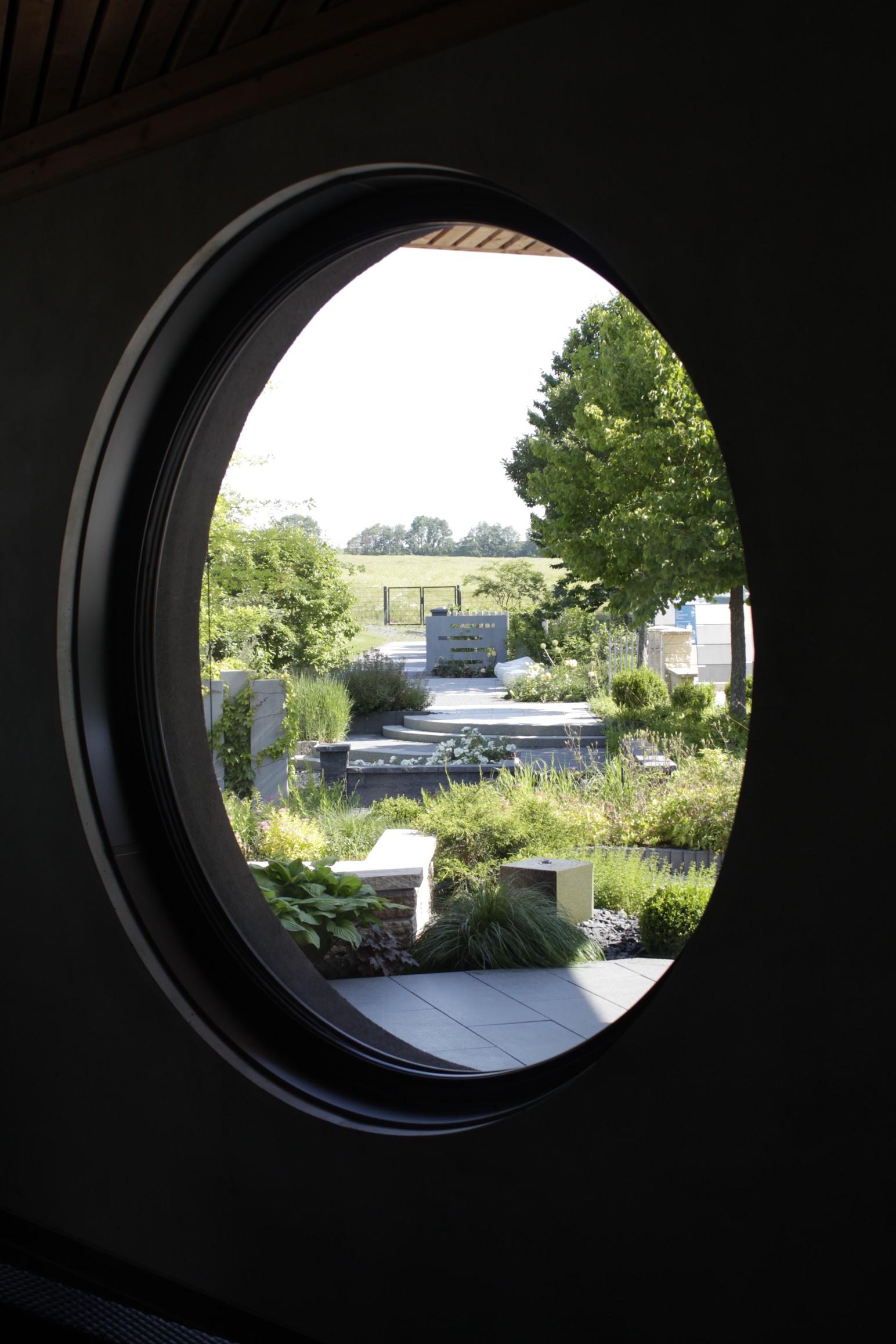 Blick durch das runde Fenster des Ideenpavillons raus ins Grüne des Ideengartens in Stadtroda.
