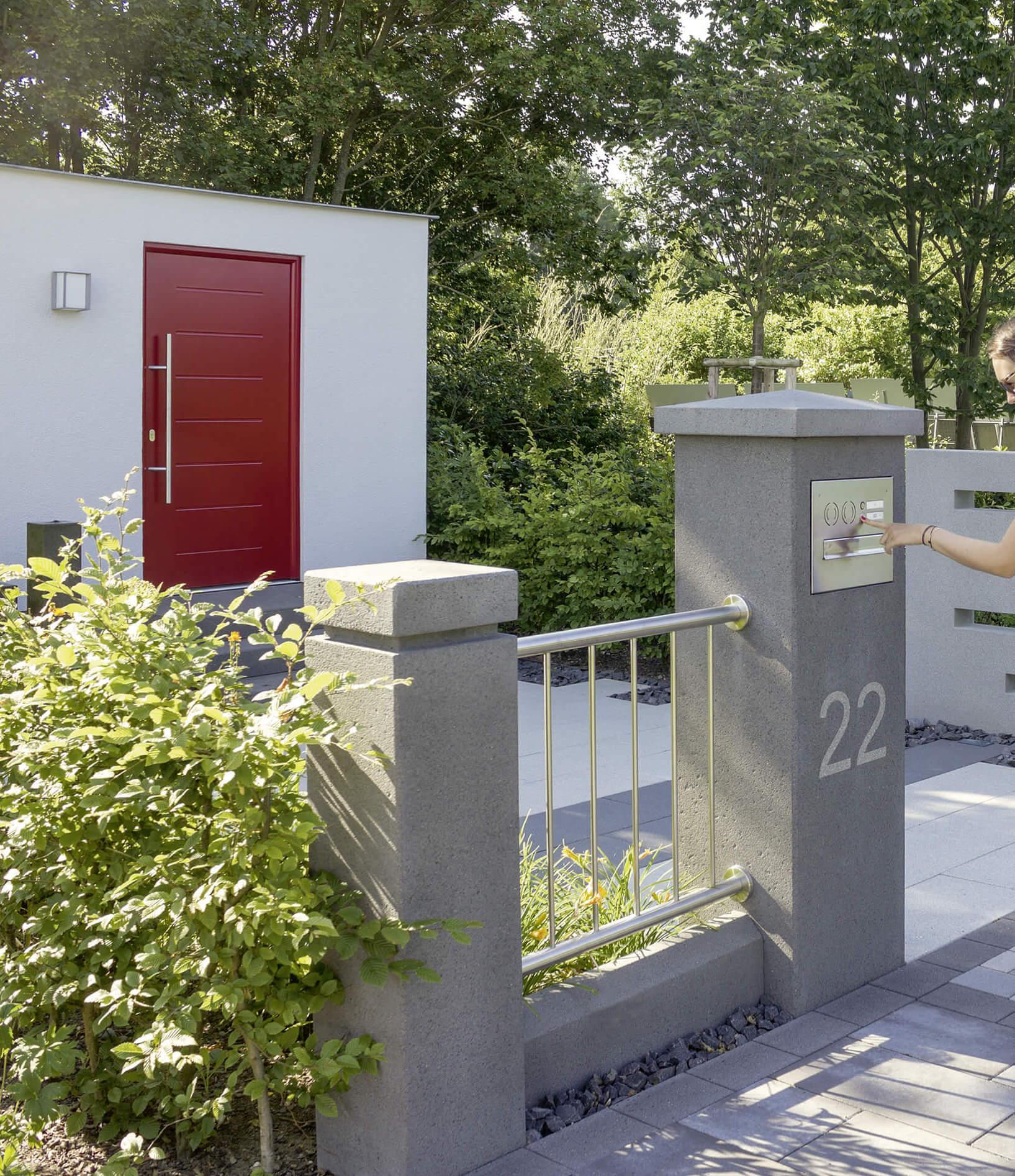 Eine Eingangssituation mit Zaun und Pfeiler mit Briefkasten und Hauseingang.
