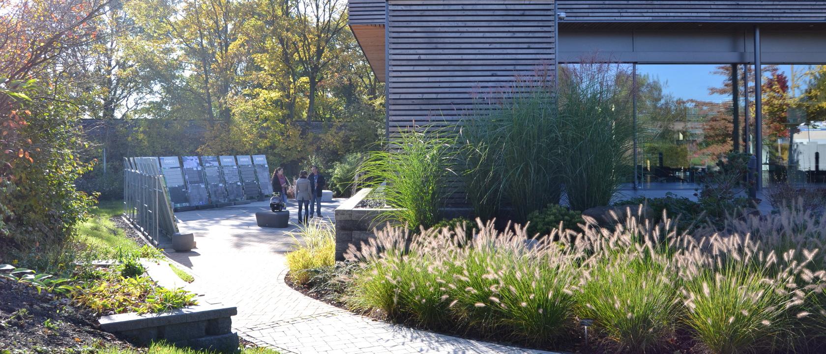 Blickl auf die Musterregale und den Ideenpavillon im Ideengarten Stadtroda. Die Gräser sind groß gewachsen und passen gut zur Holzfassade des Gebäudes.