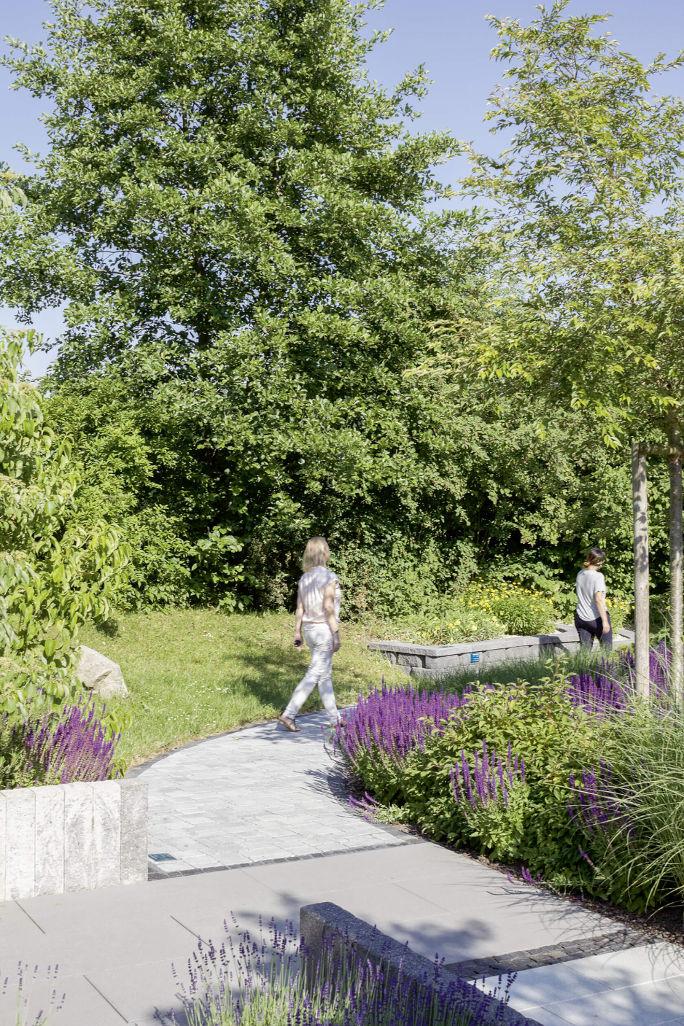 Beim Spaziergang durch den Ideengarten, auf den Wegen aus Pflastersteinen mit farbenfroher Beetbepflanzung.