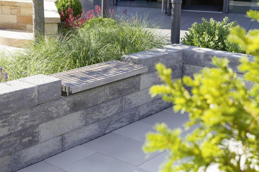 In die hellgraue Mauer mit Farbspiel ist eine Holzauflage integriert, die sich als Sitzplatz im Freien perfekt eignet.