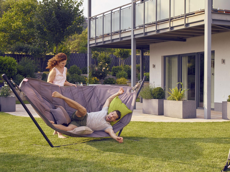 Die junge Frau wirft Ihren Freund aus der Hängematte. Hier lag er entspannt im Garten.