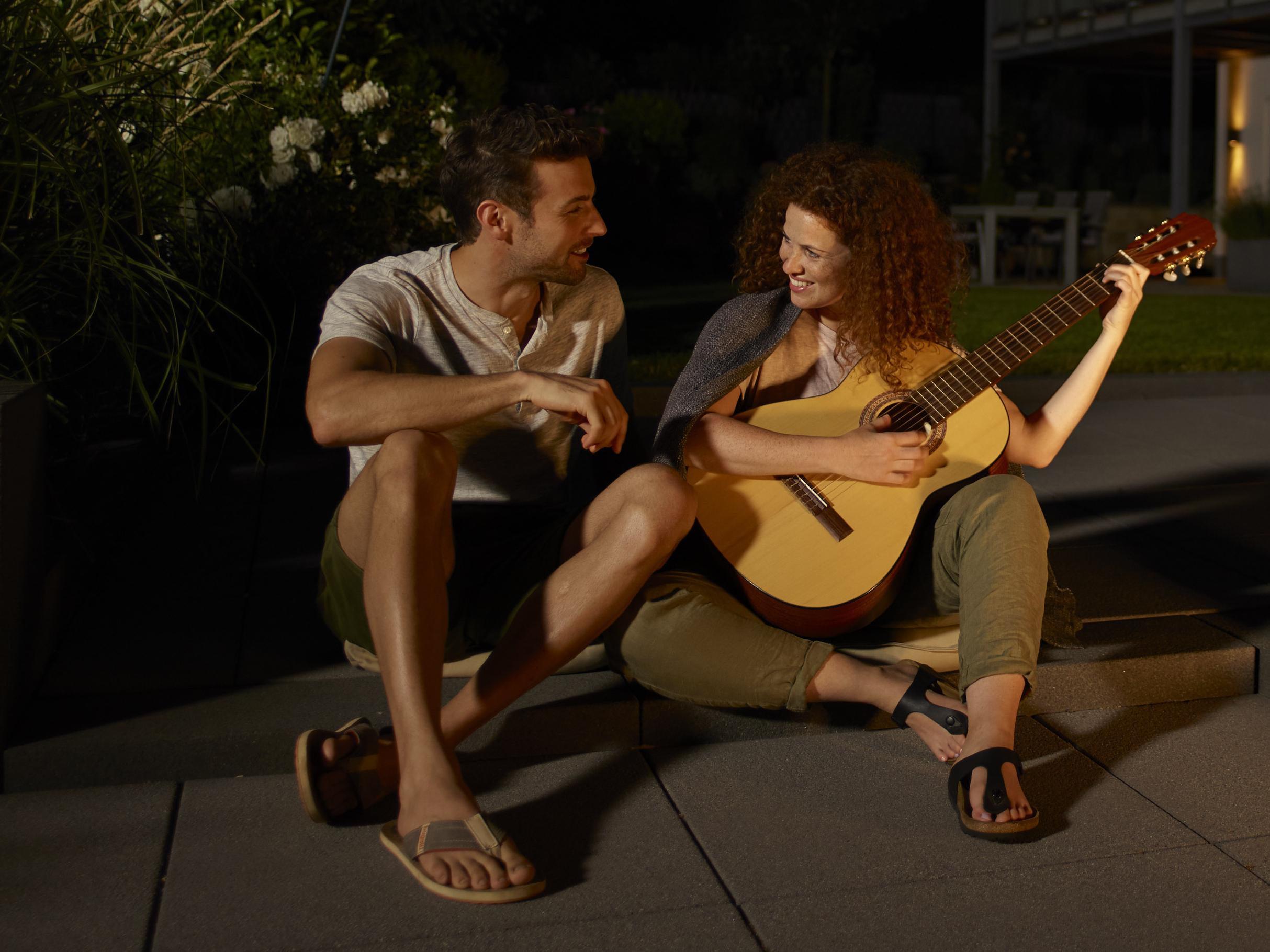 Ein junges Paar sitzt entspannt an der Feuerstelle im Garten und spielt bis in die dunkle Nacht hinein auf der Gitarre.
