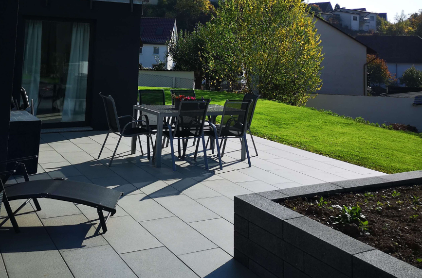 Neugebaute Terrasse am Neubauhaus mit grauen Terrassenplatten und vielen Sitzmöbeln.
