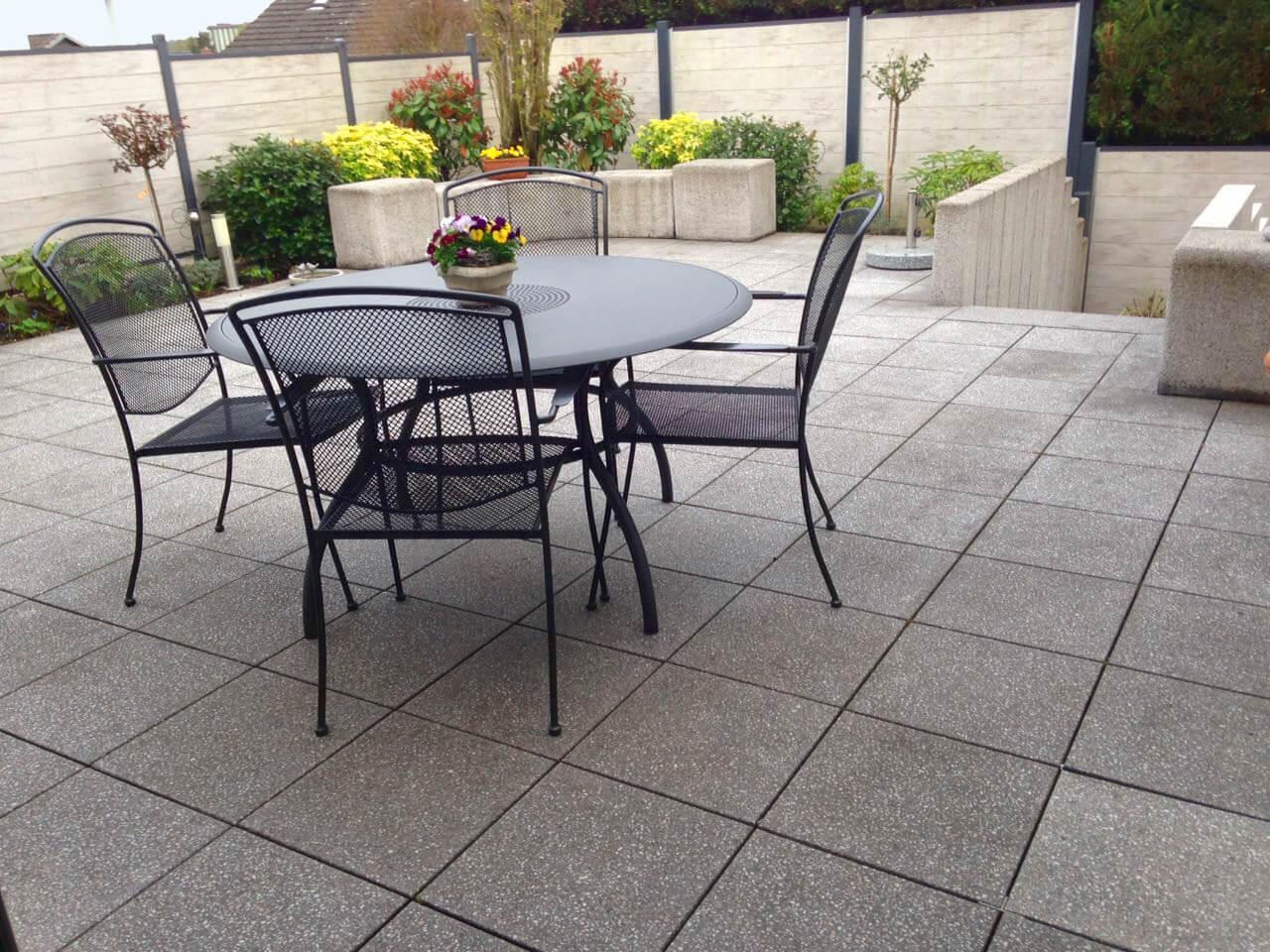 Blick auf die Terrassensituation vor der Reinigung. Die Verwitterungsspuren an Platten, Sitzblöcken und Stelen sind erkennbar.