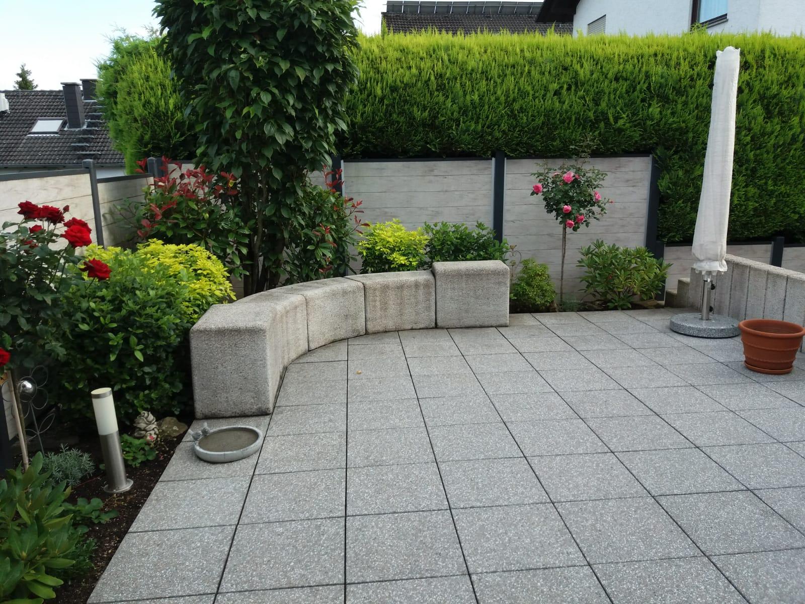 Blick auf die Terrasse vor der Reinigung: Den Sitzblöcken und Terrassenplatten sieht man ihr Alter an.
