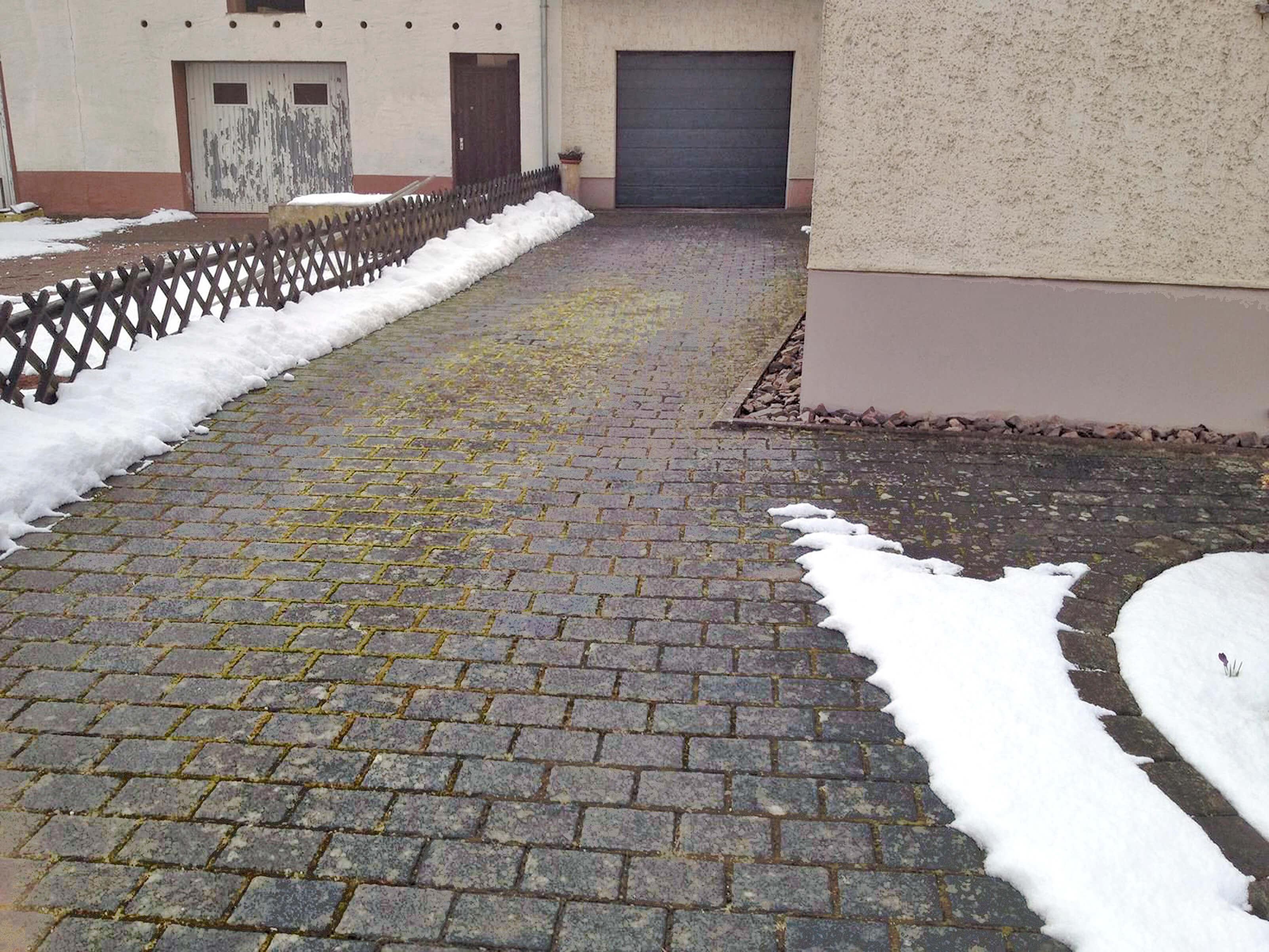 Die fleckige, verdreckte Einfahrt sieht nicht mehr schön aus. Die Pflastersteine sind kaum noch erkennbar.
