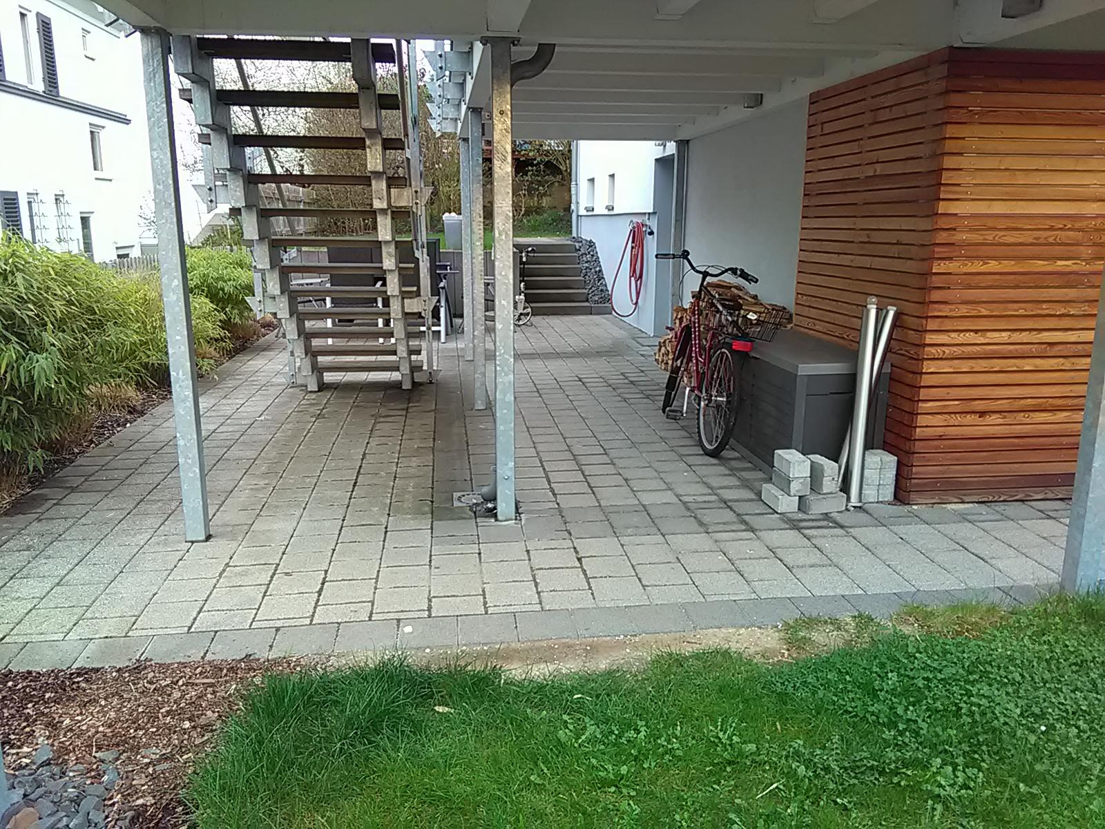 Besonders unter der Treppe, die zum Balkon führt, sind die Pflastersteine auf dem überdachten Sitz- und Lagerbereich im Garten stark verschmutzt.