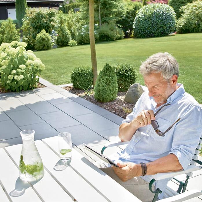 Ein Mann liest auf einem Tablett auf der Terrasse.