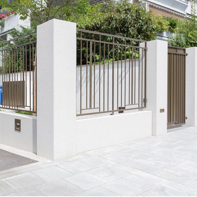 Helle Betonpfeiler als Zaun, Metallelemente verbinden die Zaunpfeiler.