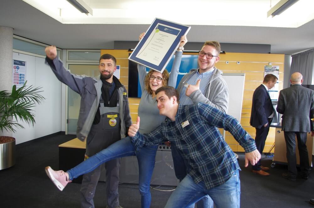 Drei Auszubildende aus dem kaufmännischen udn gewerblichen Bereich halten die Auszeichnung der IHK in den Händen.