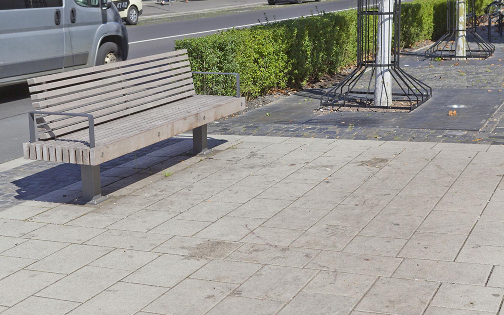 Eine Bank auf einem öffentlichen Platz mit verschmutzten Betonsteinen.
