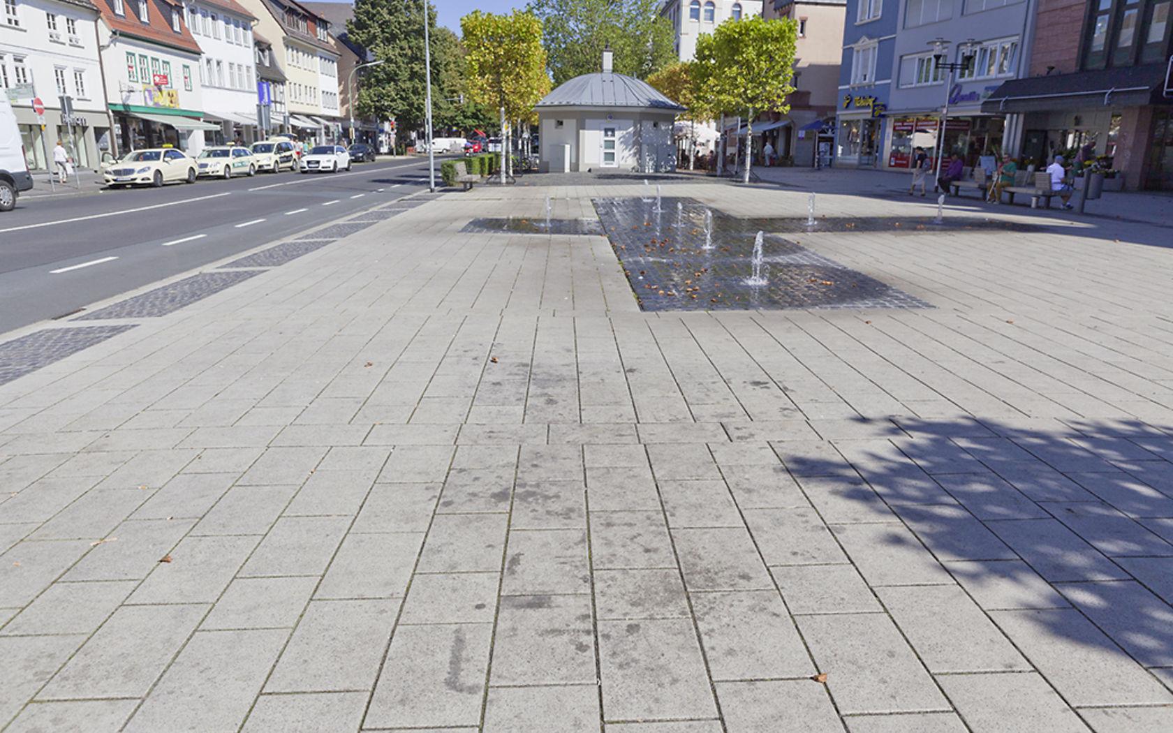 Kaugummiflecken und andere Verschmutzungen auf dem Platz mit Brunnenanlage.